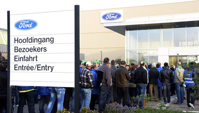 Workers at the entrance to Ford car factory in Genk, Belgium, as Ford announced it will shut the money-losing plant in 2014.