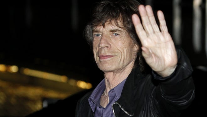Rolling Stones singer Mick Jagger waves to fans as he arrives at La Trabendo in Paris on Thursday.