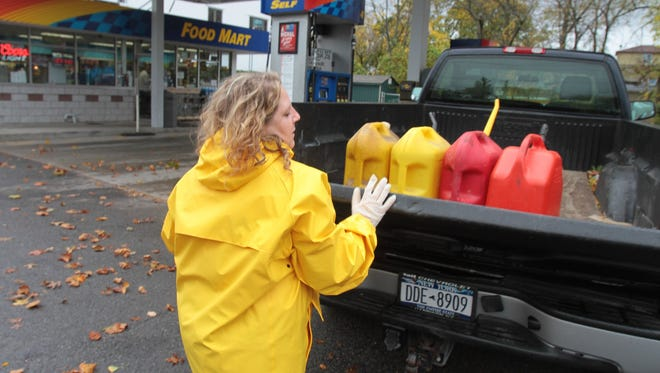 Michele Rosenshein, an employee at the Mamaroneck Beach and Yacht Club, closes the tailgate of a truck after filling gas cans, used to power a generator in Mamaroneck, N.Y.