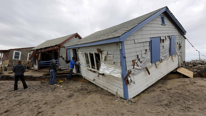 People inspect damage to cottages at Roy Carpenter's Beach by the storm surge of Hurricane Sandy in Kingstown, R.I.