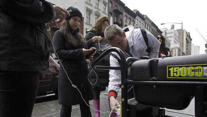 People in New York's Tribeca neighborhood, without power because of superstorm Sandy, wait for a chance to charge their mobile phones on an available generator setup on a sidewalk on Tuesday.