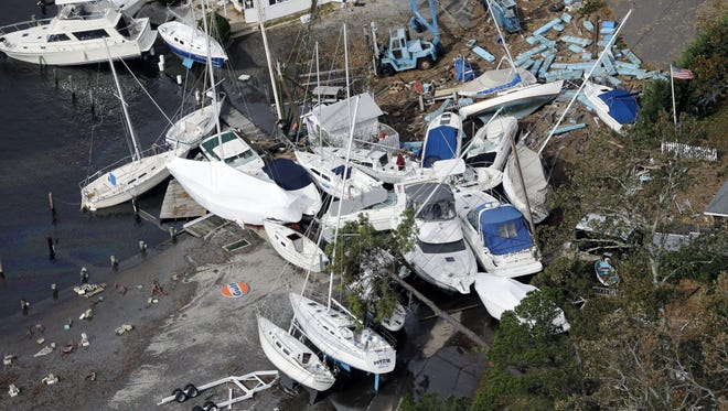 Upended boats are piled together at a marina along the central New Jersey shore.