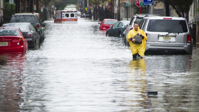 A resident walks through flood water and past a stalled ambulance in the  aftermath of Sandy in Hoboken, N.J.