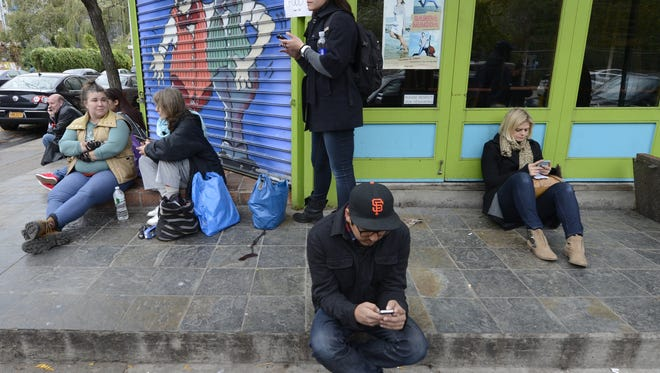 East Village residents sit on corner of Avenue C that gets cellphone reception to make calls.