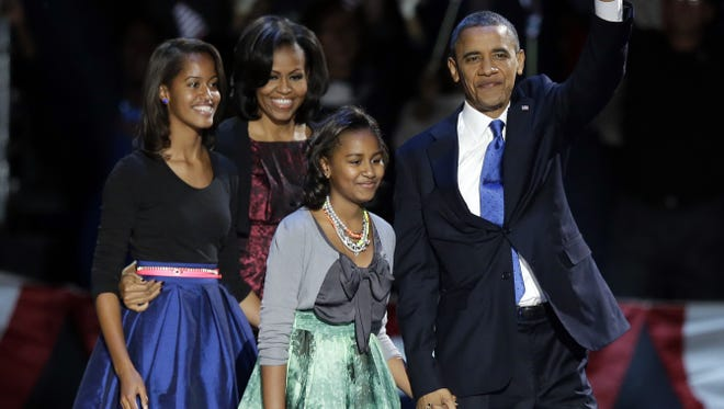 President Obama waves as he walks on stage with first lady Michelle and daughters Malia and Sasha at his election night party Wednesday, Nov. 7, 2012, in Chicago.