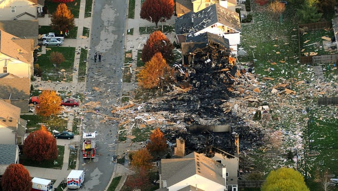 This aerial photo shows the two homes that were leveled and the numerous neighboring homes that were damaged from a massive explosion that sparked a huge fire and killed two people Sunday in Indianapolis.