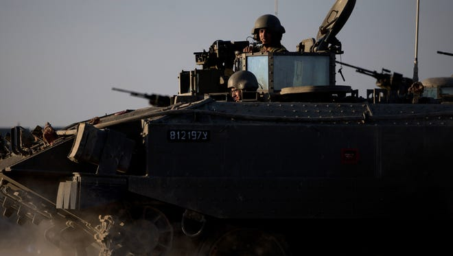 Israeli soldiers ride on top of an armored carrier close to the Israel-Gaza border on Thursday.