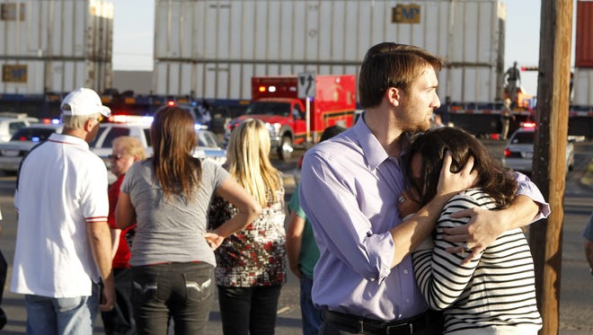 Bystanders react as emergency personnel work the scene where a trailer carrying wounded veterans in a parade was struck by a train in Midland, Texas, on Thursday.