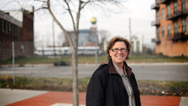 Leslie C. Horn, CEO of Three Squared, stands in the empty lot along Michigan Avenue in the historic Corktown neighborhood of Detroit on Nov. 14, 2012, where her company plans to build a 20-unit condo project using empty shipping containers. (Gannett, Kimberlhy P. Mitchell/Detroit Free Press)