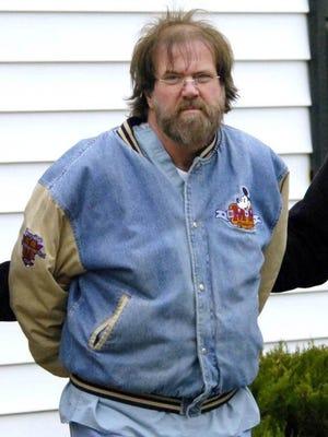 Former pediatrician Earl Bradley, shown Dec. 18, 2009, in police custody, is now serving 14 life sentences for child rape.