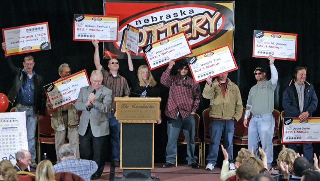 The eight winners of the $365 million Nebraska Powerball lottery in 2006 hold up their ceremonial checks at a news conference.