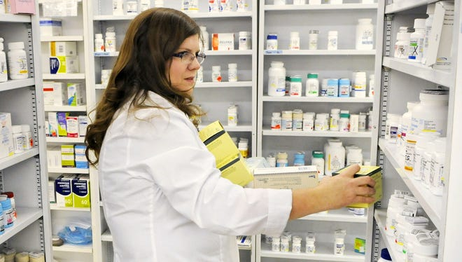 Jayne Carter, pharmacist in charge at Country Store & Pharmacy in Sartell, MInn., stocks birth control pills behind the counter on Nov. 27.