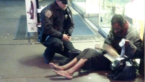 NYPD officer Lawrence DePrimo gives boots to a man on the street. Jennifer Foster of Arizona, who was visiting Times Square on Nov. 14, snapped the photo.
