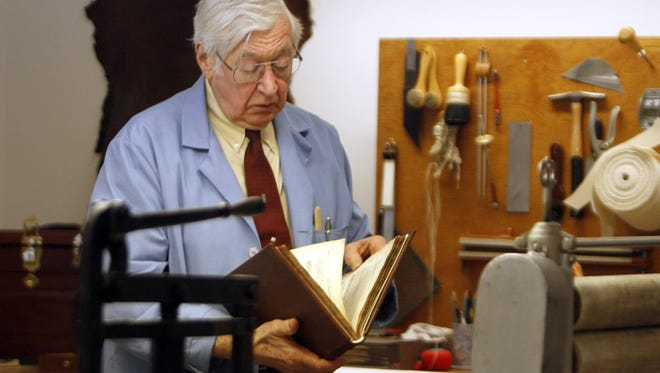 James Craven, a bookbinder and conservator, looks over a book he restored and bound at the University of Michigan Bentley Library in Ann Arbor Mich. on Nov. 28.