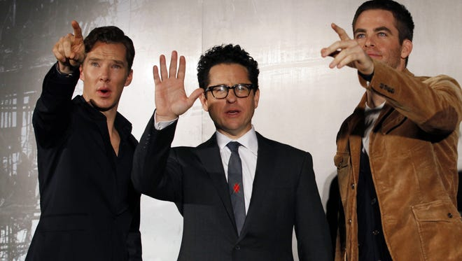 Benedict Cumberbatch, left, director J.J.  Abrams and actor Chris Pine wave during a news conference for 'Star Trek Into Darkness.'