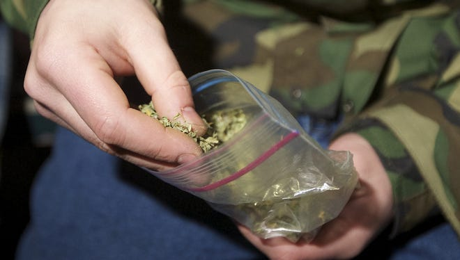 A Seattle resident removes marijuana from a plastic bag. Washington and Colorado became the first states to vote to decriminalize and regulate the possession of an ounce or less of marijuana by adults over 21. Both measures call for setting up state licensing schemes for pot growers, processors and retail stores.