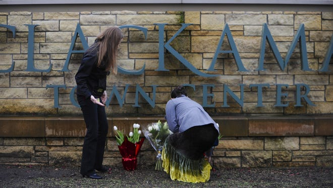 Leslie King, right, and Tenille Beseda place flowers at the entrance to Clackamas Town Center mall in Oregon.