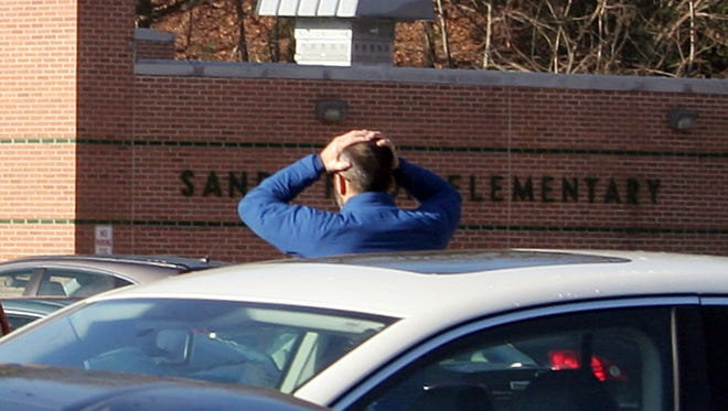 In this photo provided by the Newtown Bee, a man stands with his hands on his head outside of Sandy Hook Elementary School in Newtown, Conn., Friday.