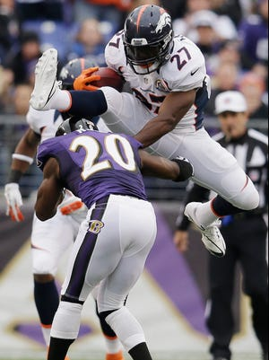 Denver Broncos running back Knowshon Moreno leaps over Baltimore Ravens free safety Ed Reed during the first half of the Broncos' win at M&T Bank Stadium on December 16, 2012 in Baltimore, Md.