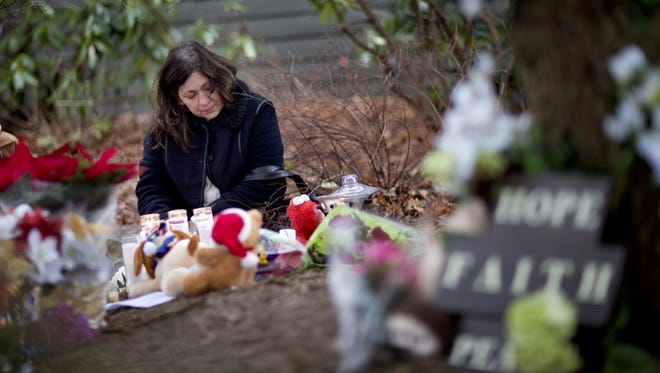 Dilma Steiner, of Newtown, Conn., visits a sidewalk memorial for the Sandy Hook Elementary School shooting victims, Sunday, Dec. 16, 2012, in Newtown, Conn. A gunman walked into Sandy Hook Elementary School in Newtown Friday and opened fire, killing 26 people, including 20 children. (AP Photo/David Goldman) ORG XMIT: CTDG117