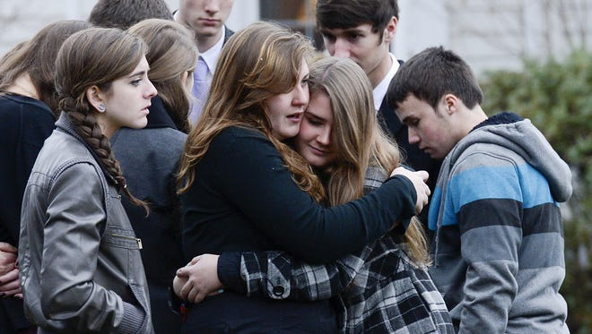 Mourners embrace after a funeral for Noah Pozner at the Green Funeral Home in Fairfield, Conn., on Monday.