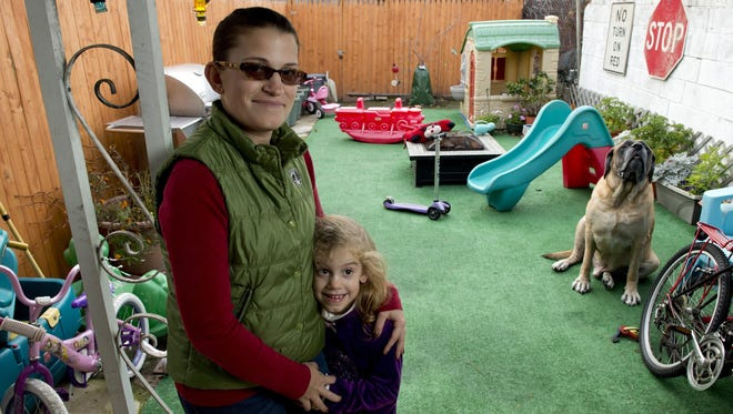 Christina DiPietro-Sokol has covered the family's backyard in artificial turf to keep daughter Amelia and their dog, Hobbes, from coming into contact with the dirt.  The family lives a few blocks from the former John T. Lewis-National Lead-Anzon factory site in Philadelphia. The EPA met with neighborhood residents this year to alert them that soil tests had found high levels of lead in the yards of some homes in the area.