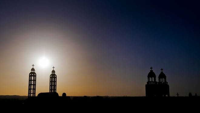 In this Tuesday, Dec. 18, 2012 photo, towers of churches are silhouetted against the sun in the village of El-Aziyah near the city of Assiut, southern Egypt.