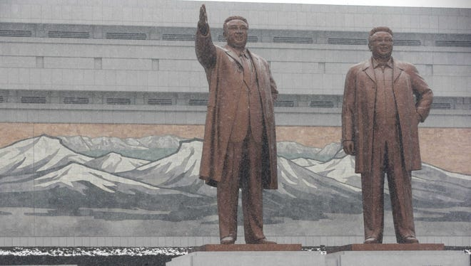 A man walks past the statues of late North Korean leaders Kim Il Sung, left, and Kim Jong Il at Mansu Hill as it snows in Pyongyang, North Korea, on Friday.