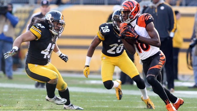 Cincinnati Bengals wide receiver A.J. Green (18) runs after a pass reception as Pittsburgh Steelers strong safety Troy Polamalu (43) and strong safety Will Allen (26) defend during the second quarter at Heinz Field.