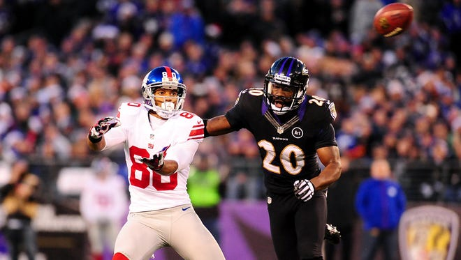 New York Giants wide receiver Victor Cruz (80) reaches for a pass while being defended by Baltimore Ravens safety Ed Reed (20) at M&T Bank Stadium.