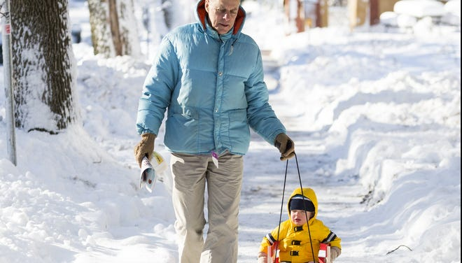 Frank Gloss pulls along his 17-month-old grandson, Liam, on Friday in Madison, Wis., a day after the state was blanketed with a record snowstorm.