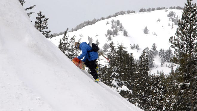 A snowboarder follows a friend on March 22, 2011, up a steep backcountry slope near the Mount Rose Highway summit in Nevada in the Sierra.