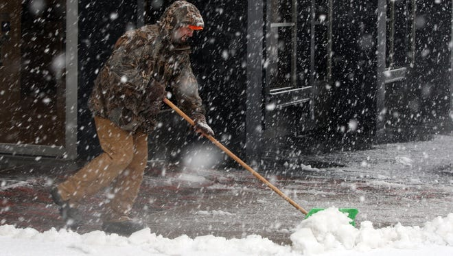 Brad Johnson pushes the heavy snow off the sidewalk in the blowing snow Dec. 20 in downtown Burlington, Iowa.