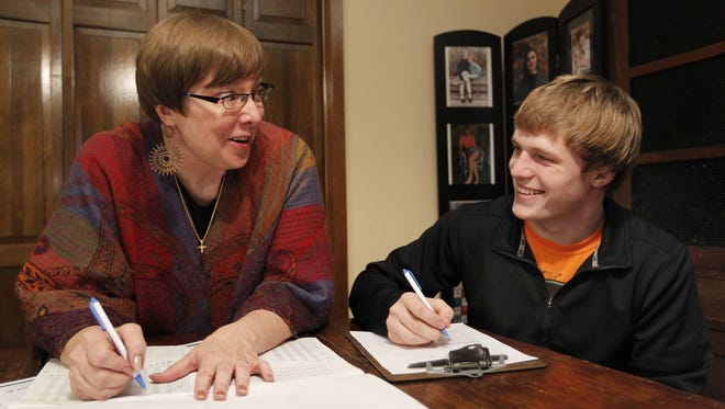 "Ramona Barber, left, known as the ""teen whisperer,"" works with Rick Maris, 18, in her West Des Moines, Iowa home on Dec. 18."