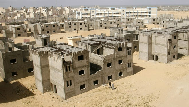 Palestinians pass by unfinished buildings at the UNRWA housing project in Khan Younis, southern Gaza Strip in 2011.