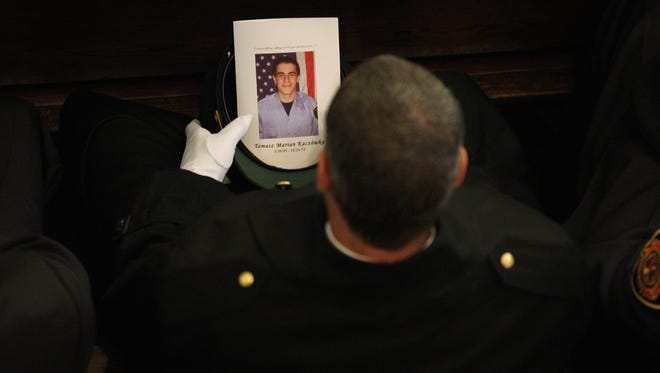A West Webster firefighter carries a program during the funeral for fellow West Webster firefighter Tomasz Kaczowka at St. Stanislaus Church in Rochester, N.Y., Monday.