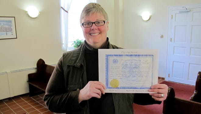 Kim Hinken, of Edgewater, Md., holds the marriage license she obtained Thursday in Anne Arundel County Circuit in Annapolis, Md., to marry her same-sex partner, Adrianne Eathorne.