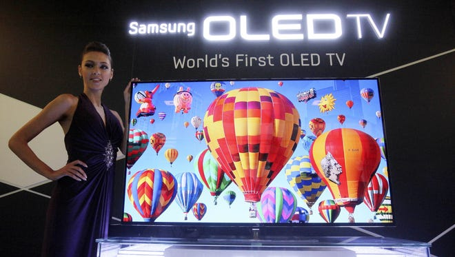 A model poses with a 55-inch Samsung OLED, organic light-emitting diode, TV during a press conference in Seoul, South Korea on May 10.