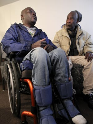 Marcelous Pierre, left, chats with Julio Racine in Louisville, Ky., on January 4. The 2010 Haitian earthquake killed one of his children and severed his spinal cord, leaving him a medical refugee in Louisville.