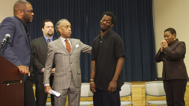 The Rev. Al Sharpton, center, comforts Anthony Denson Jr. during a Thursday news conference in Naples, Fla. Entertainer Tyler Perry, left, offered a $100,000 reward for tips leading to arrest related to the cases of missing men Terrence Williams and Felipe Santos. Williams' mother, Marcia Williams, is on the right. NAACP President  Ben Jealous is in the background.