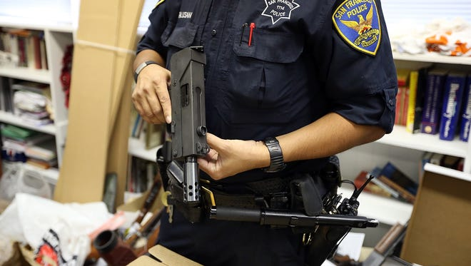 A San Francisco police officer inspects a gun that is being surrendered during a gun buy back program on December 15.