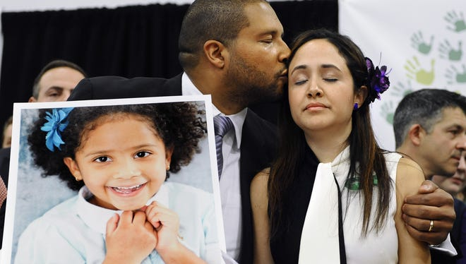 Jimmy Greene, left, kisses his wife, Nelba Marquez-Greene, as he holds a portrait of their daughter, Ana, at a Monday news conference in Newtown, Conn. Ana was killed in the shooting spree at Sandy Hook Elementary School.