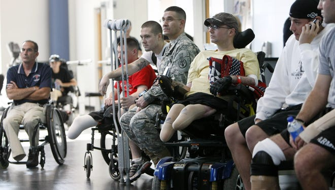 In this Nov. 8, 2007 file photo, wounded soldiers involved in physical therapy wait for President Bush to visit a physical therapy lab for wounded soldiers at the Center For The Intrepid at the Brooke Army Medical Center in San Antonio.