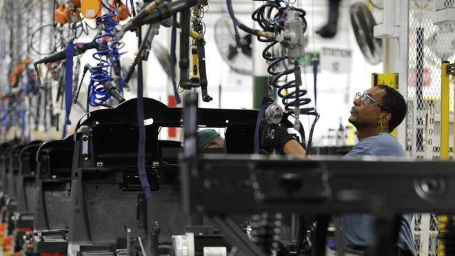 In this Thursday, July 19, 2012, photo, assembler Barry Austin works on a golf car production line at the E-Z-GO plant in Augusta, Ga.