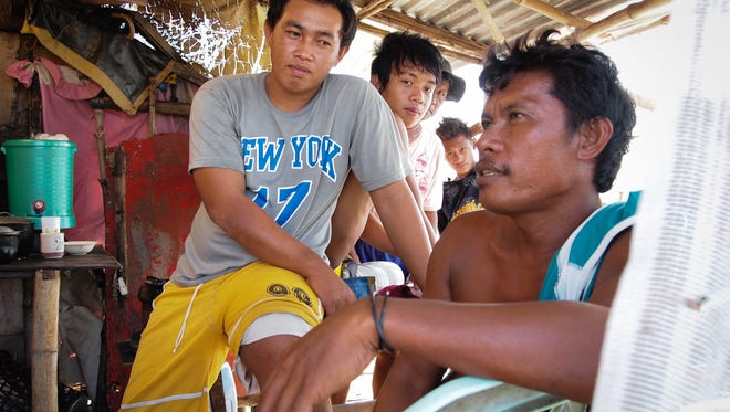 Romeo Taneo, right, 39, a fisherman in Masinloc, discusses his loss of income because of the Chinese presence at Scarborough Shoal.