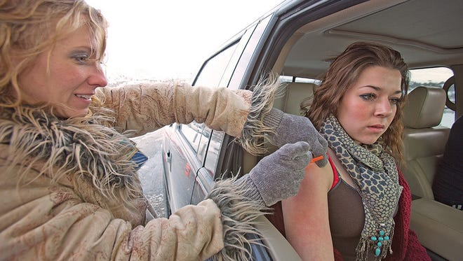 Lexie Nielson, 15, is given an influenza innoculation by Becky Jones, Northeastern Nevada Regional Hospital director of nursing, in Elko, Nev. Doctors and nurses in northeastern Nevada battled the frigid weather this week to provide hundreds of free flu shots at a temporary vaccine drive-thru clinic.