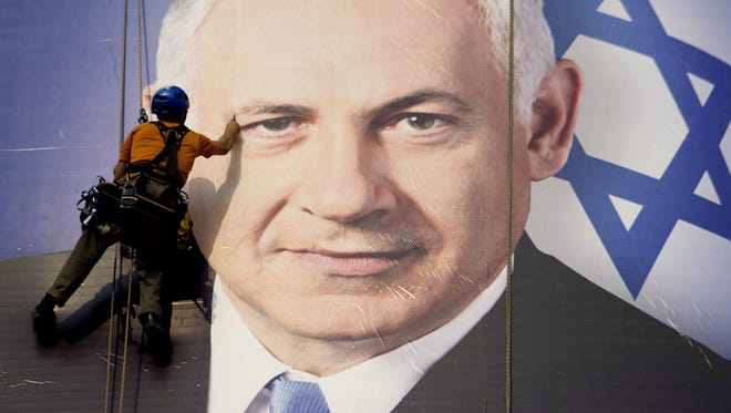 A worker hangs a huge poster with an image of Israel's Prime Minister Benjamin Netanyahu in Tel Aviv.