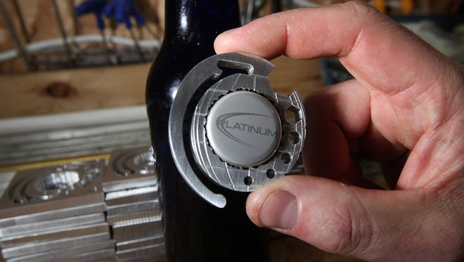 Webster City, Iowa electrician and inventor Brad Martin recently displays his grenade-shaped bottle opener on January 8.