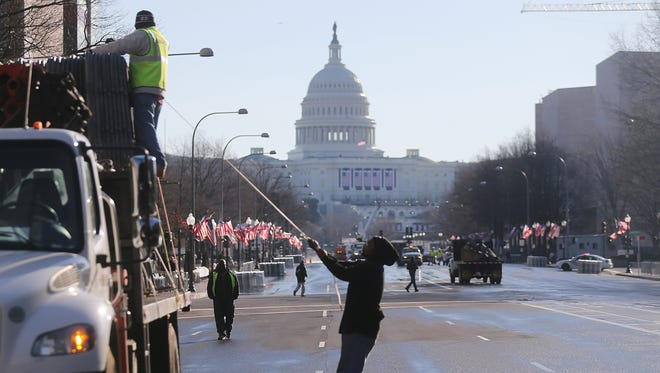 Workers prepare the parade route along Pennsylvania Avenue for Monday's Inaugural Parade.