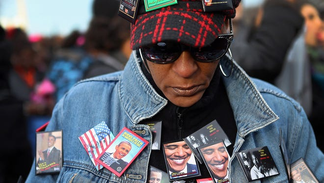 Lisa Hogue is nearly covered in pins as she and others gather near the U.S. Capitol for the inauguration ceremony Monday.